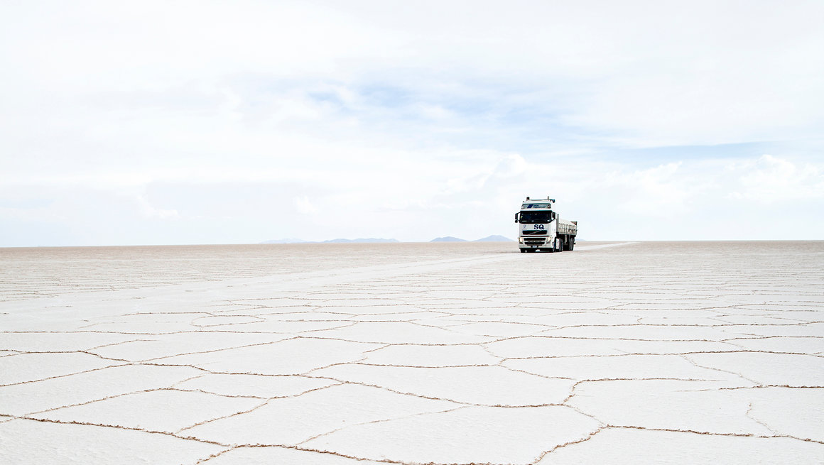 Truck driving through salt flat.