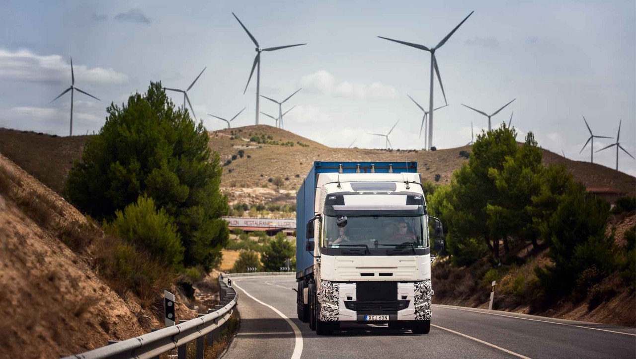 A test truck on the road in Spain with wind turbines in the background