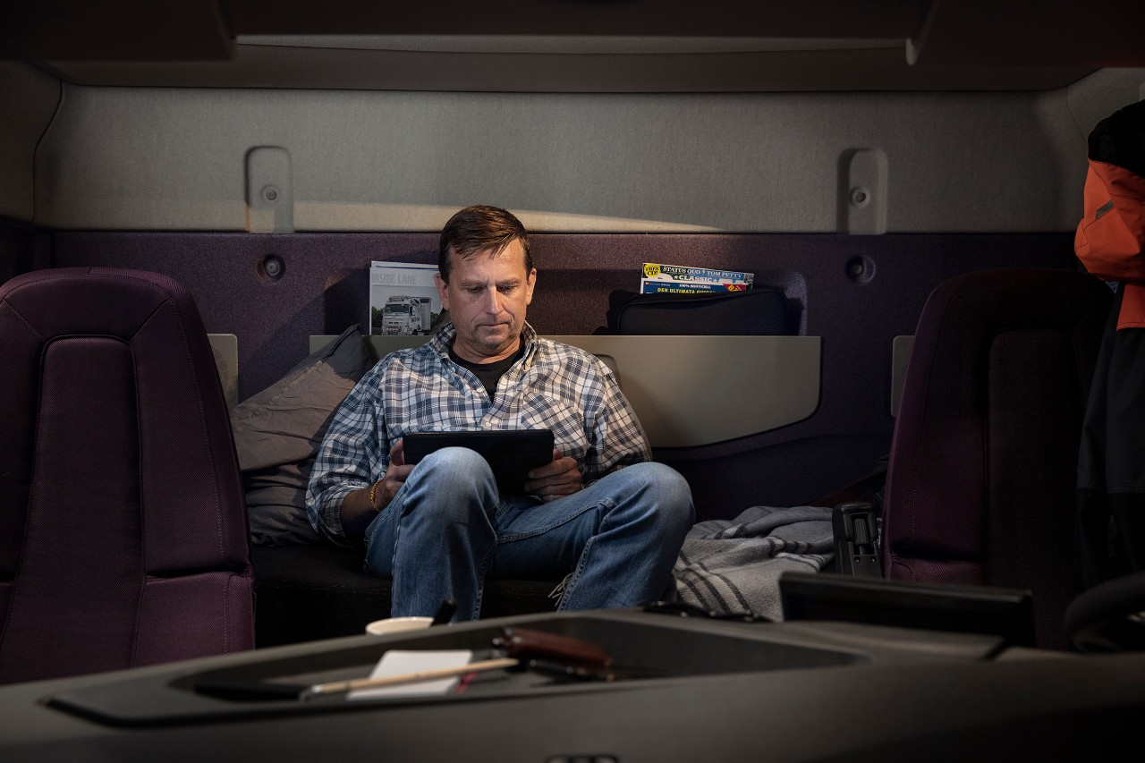 A man reclines as he looks at an iPad